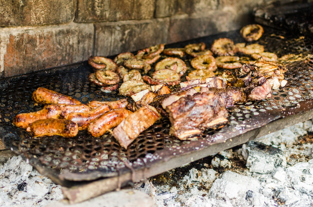 Traditional Argentina asado grilled meat barbecue. Chorizo sausages, ribs, and intestines on a parilla grill.